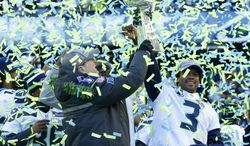 Seattle Seahawks owner Paul Allen, left, lifts the Vince Lombardi Trophy with Seahawks quarterback Russell Wilson (3) during a rally on Wednesday, Feb. 5, 2014, in Seattle. The Seahawks defeated the Denver Broncos on Sunday in NFL football's Super Bowl XLVIII game in East Rutherford, N.J. (AP Photo/Ted S. Warren)