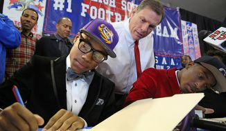 John Curtis head football coach J.T. Curtis, left, watches as Malachi Dupre signs his letter of intent for LSU at the John Curtis High School gym on National Signing Day, Wednesday, Feb. 5, 2014. (AP Photo/The Times-Picayune, Julia Kumari Drapkin) **FILE**