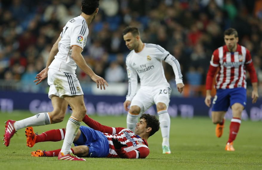 Atletico's Diego Costa, centre falls to the ground during a semi final, 1st leg, Copa del Rey soccer derby match between Real Madrid and Atletico Madrid at the Santiago Bernabeu Stadium in Madrid, Wednesday Feb. 5, 2014.  (AP Photo/Paul White)
