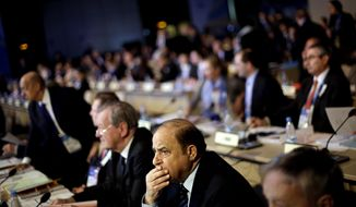International Olympic Committee member Samih Moudallal, of Syria, waits for the IOC's general assembly to convene on its first day at the 2014 Winter Olympics, Wednesday, Feb. 5, 2014, in Sochi, Russia. (AP Photo/David Goldman)