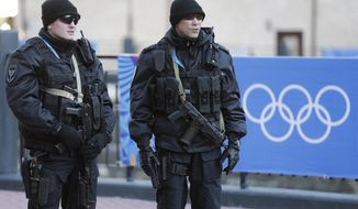 Russian security forces stand guard as the Olympic torch makes it's way through the streets of the Rosa Khutor ski resort in Krasnaya Polyana, Russia at the Sochi 2014 Winter Olympics, Wednesday, Feb. 5, 2014. (AP Photo/Gero Breloer)