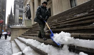 U.S. Parks Service employee Danny Merced clears snow from the steps of Federal Hall, in New York's Financial District, Wednesday, Feb. 5, 2014.  New York City's sanitation commissioner says some secondary streets still need plowing but overall snow removal was going well. Around 6 inches of snow are expected in parts of the metropolitan area on Wednesday. (AP Photo/Richard Drew)