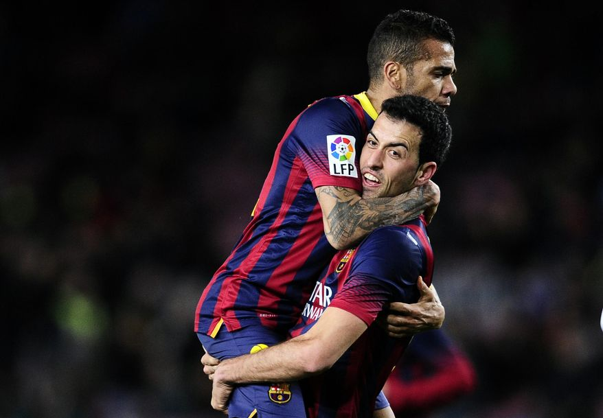FC Barcelona's Sergio Busquets, right, huges Daniel Alves, from Brazil, left after scoring against Real Sociedad during a Copa del Rey soccer match at the Camp Nou stadium in Barcelona, Spain, Wednesday, Feb. 5, 2014. (AP Photo/Manu Fernandez)
