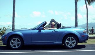 This 2006 photo released by Michael Jones shows Jennifer Jones in her Mazda Miata in Kaneohe, Hawaii.  Jones, who stopped to help after a crash on a Honolulu freeway on Sunday, Feb. 2, 2014, says two men involved in the wreck stole her car, leaving behind an injured passenger. (AP Photo/Michael Jones)