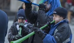 Seattle Seahawks fans Nicholas Anderson, 12, Jonathan Anderson, 14 and Jason Anderson, 12 (twin with Nicolas) toot their hawks horns trying to stay warm as they wait for the Super Bowl champions parade to begin Wednesday, Feb. 5, 2014, in Seattle. The Seahawks beat the Denver Broncos 43-8 in NFL football's Super Bowl XLVIII on Sunday. (AP Photo/The Seattle Times, Steve Ringman)  SEATTLE OUT; USA TODAY OUT; MAGAZINES OUT; TELEVISION OUT; NO SALES; MANDATORY CREDIT