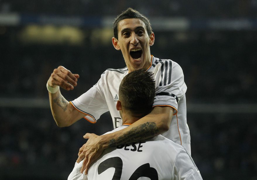 Real's Angel Di Maria, top celebrates with Real's Jese Rodriguez after Rodrigues scored during a semi final, 1st leg, Copa del Rey soccer derby match between Real Madrid and Atletico Madrid at the Santiago Bernabeu Stadium in Madrid, Wednesday Feb. 5, 2014.  (AP Photo/Paul White)