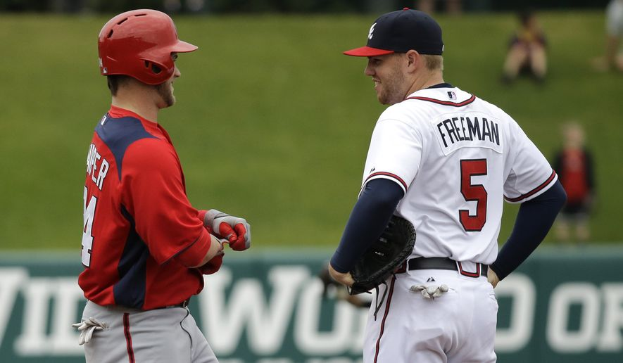Washington Nationals' Bryce Harper (34) talks with Atlanta Braves' Freddie Freeman (5) during the third inning of an exhibition spring training baseball game Tuesday, Feb. 26, 2013, in Kissimmee, Fla. (AP Photo/David J. Phillip)