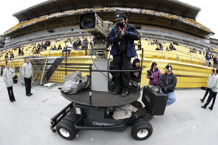 FILE - In this Nov. 10, 2013, file phot, a CBS sideline camera operator prepares for an NFL football game between the Pittsburgh Steelers and the Buffalo Bills in Pittsburgh. The NFL says CBS will televise eight of its Thursday night games next season. The leagues says the contr