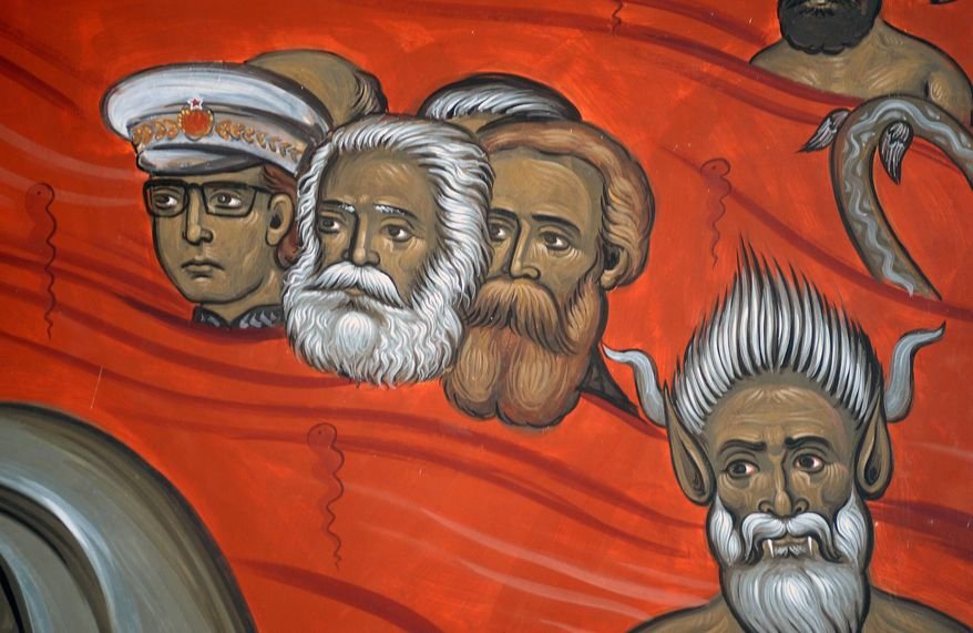 This photo taken Tuesday, Feb. 4, 2014 shows the brightly-colored newly painted fresco in the Serbian Orthodox Church of Christ's Resurrection in Montenegro's capital Podgorica. The fresco allegedly shows late Yugoslav autocratic leader Josip Broz Tito drowning in red fiery waves of hell with Karl Marx and Friedrich Engels, authors of the 1848 Communist Manifesto. They are in the company of Adam and Eve, together with some of Montenegro's current politicians and people wearing Muslim turbans. What appear to be rival church priests are being swallowed through a huge jaw of an angry gray beast with pointed devil ears. The fresco has triggered much attention and public controversy in this tiny former communist country. (AP Photo/Risto Bozovic)
