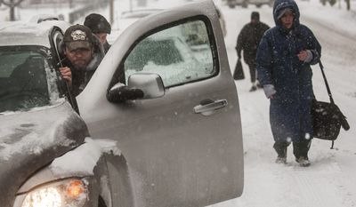 William Thompson, 43, of Flint, Mich., front left, pushes his car out of the snow with the help from Ryan Beuthin, 30, Wednesday, Feb. 5, 2014, in Flint, Mich. (AP Photo/The Flint Journal, Jake May) LOCAL TV OUT; LOCAL INTERNET OUT