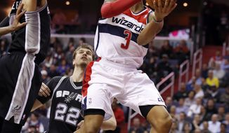 Washington Wizards guard Bradley Beal (3) looks to pass as he is guarded by San Antonio Spurs guard Danny Green (4) and center Tiago Splitter (22), from Brazil, in the first half of an NBA basketball game on Wednesday, Feb. 5, 2014, in Washington. (AP Photo/Alex Brandon)