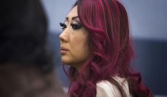 Gloria Lee, 35, who is facing charges of arson following a Jan. 27 fire at her Prince and Princess Pet Boutique in Las Vegas, appears in Clark County Justice Court Wednesday, Feb. 5, 2014, in Las Vegas. Lee surrendered her passport at the demand of Justice of the Peace Joe Sciscento. A total of 27 puppies were rescued and taken to the shelter after the attempted arson. (AP Photo/Las Vegas Review-Journal, Jeff Scheid) LOCAL TV OUT; LOCAL INTERNET OUT; LAS VEGAS SUN OUT