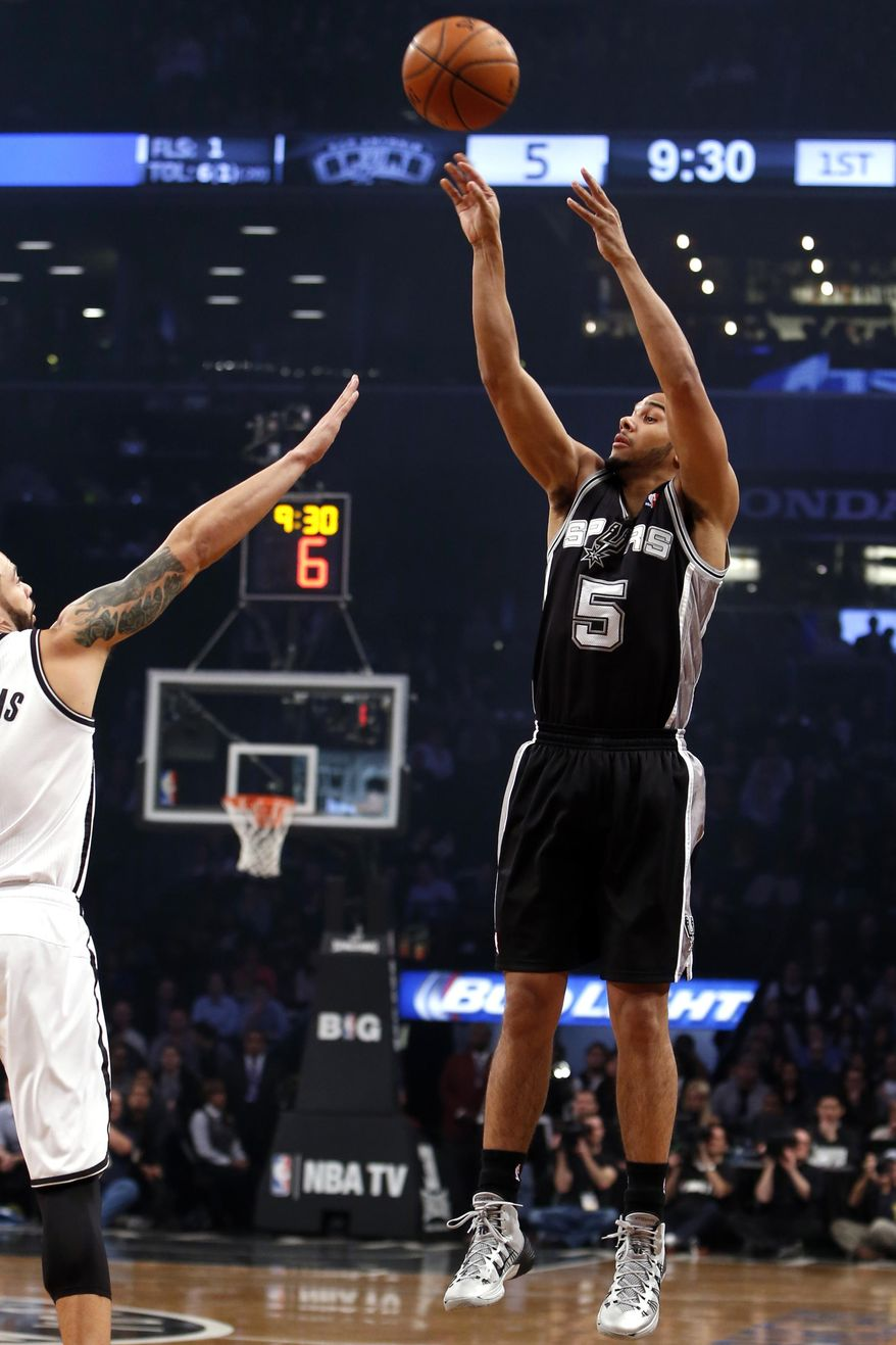 San Antonio Spurs' Cory Joseph (5) shoots against Brooklyn Nets' Deron Williams during the first half of an NBA basketball game on Thursday, Feb. 6, 2014, in New York. (AP Photo/Jason DeCrow)