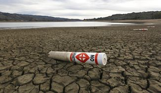 In this photo taken Tuesday, Feb. 4, 2014, a warning buoy sits on the dry, cracked bed of Lake Mendocino near Ukiah, Calif.  Despite recent spot rains The reservoir is currently only about 37 percent full.  California remans in the midst of an historic drought causing Gov. Jerry Brown to declare a state of emergency.(AP Photo/Rich Pedroncelli)