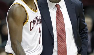 Cleveland Cavaliers head coach Mike Brown, right, talks to Kyrie Irving in the first quarter of an NBA basketball game against the Los Angeles Lakers, Wednesday, Feb. 5, 2014, in Cleveland. (AP Photo/Mark Duncan)