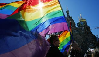 In this Wednesday, May 1, 2013, file photo, gay rights activists carry rainbow flags as they march during a May Day rally in St. Petersburg, Russia. (AP Photo/Dmitry Lovetsky, File)