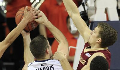 Virginia guard Joe Harris (12) is fouled by Boston College forward Eddie Odio, right, as he goes up for a shot during the first half of an NCAA college basketball game in Charlottesville, Va., Wednesday, Feb. 5, 2014. (AP Photo/Steve Helber)