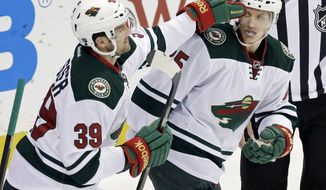 Minnesota Wild's Nate Prosser, left, gives a tap on the helmet to Minnesota Wild's Jonas Brodin of Sweden after Brodin scored against Nashville Predators goalie Carter Hutton in the first period of an NHL hockey game, Thursday, Feb. 6, 2014, in St. Paul, Minn. (AP Photo/Jim Mone)