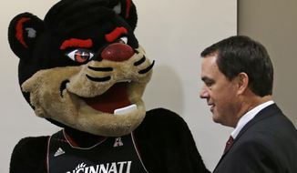 Mike Bohn walks past the school mascot as Bohn was introduced as Cincinnati athletic director, Thursday, Feb. 6, 2014, in Cincinnati. Bohn had been athletic director at Colorado from 2005 to 2013. (AP Photo/Al Behrman)