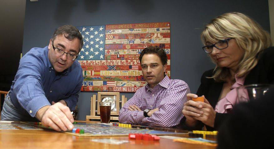 In this photo taken Thursday, Jan. 9, 2014, Spirit Airlines CEO Ben Baldanza center, and DeAnne Gabel, director Investor relations, right, play a game of Power Grid at Baldanza's home, in Fort Lauderdale, Fla. (AP Photo/Alan Diaz)