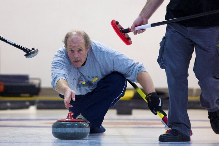 Eye-catching: George Shirk delivers the stone down the sheet at the Potomac Curling Club. Curling has become an Olympic sport for the common man, and the club sponsors leagues for those who become fans after watching it on television. (Preston Keres/Special to The Washington Times)