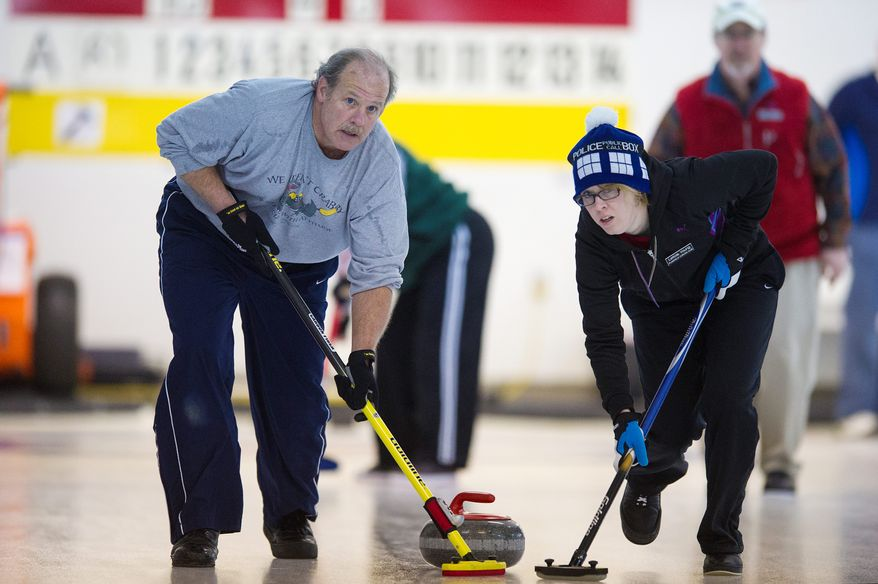 George Shirk of the Potomac Curling Club and Leticia Young of the Plainfield Curling Club compete in the games held in Laurel, Md. (Preston Keres/Special to The Washington Times)