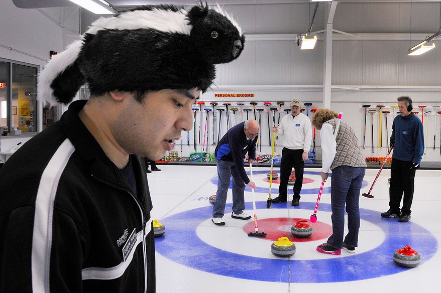 Mind game: Eugene Huang of the Plainfield Curling Club in New Jersey keeps an eye on his team's sheet as others sweep for a score during the competition.