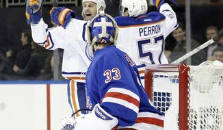 Edmonton Oilers' Ryan Smyth (94) celebrates with teammate David Perron (57) as New York Rangers goalie Cam Talbot (33) watches after Smyth scored during the first period of an NHL hockey game on Thursday, Feb. 6, 2014, in New York. (AP Photo/Frank Franklin II)