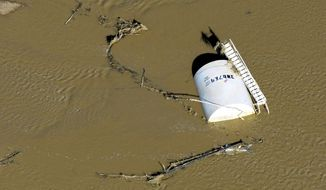 File - In this Sept. 17, 2013, file photo, a crude oil storage tank lies on its side in flood water along the South Platte River in Weld County, Colo. Oil and gas regulators are discussing whether to create new rules after more than a dozen spills of petroleum products were blamed on major flooding last September. (AP Photo/John Wark, file)