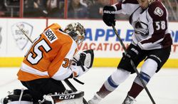 Philadelphia Flyers' Steve Mason, left, gloves the puck as Colorado Avalanche'  Patrick Bordeleau, right, moves in during the first period of an NHL hockey game, Thursday, Feb. 6, 2014, in Philadelphia. (AP Photo/Tom Mihalek)