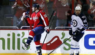 Washington Capitals right wing Troy Brouwer (20) celebrates his goal in front of Winnipeg Jets right wing Devin Setoguchi (40) during the first period of an NHL hockey game, Thursday, Feb. 6, 2014, in Washington. (AP Photo/Alex Brandon)