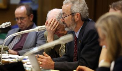 Administrative counsel Bill Taylor holds his head in his hands next to Sen. Floyd Prozanski as they hear testimony at the Senate Judiciary Committee at a public gun bill hearing in Hearing Room 50 at the State Capitol in Salem, Ore.,  Thursday Feb. 6, 2014. The hearing concerns a bill to expand background checks for firearms sales. AP Photo/Kobbi R. Blair, Statesman Journal