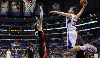 Los Angeles Clippers forward Blake Griffin, right, goes up for a dunk as Miami Heat forward Chris Andersen, center, defends and forward LeBron James, second from left, and forward Matt Barnes watch during the first half of an NBA basketball game, Wednesday, Feb. 5, 2014, in Los Angeles. (AP Photo/Mark J. Terrill)