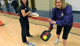 ADVANCE FOR USE SATURDAY, FEB. 8 AND THEREAFTER - In this Jan. 23, 2014, 2014 photo, Carol Drake, right, serves during a pickleball game demonstration, with Four Seasons Health Club membership manager Dona Lenz looking on in Bloomington, Ill. The game is a cross between tennis, badminton and pingpong: The court is the size of a badminton court, players use a paddle that is slightly bigger than a pingpong paddle and the ball is a whiffle ball about the size of a tennis ball. A 3-foot-tall net divides the court. (AP Photo/The Pantagraph, Steve Smedley)