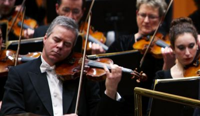 In this undated photo provided by the Milwaukee Symphony Orchestra  concertmaster Frank Almond plays a 300-year-old Stradivarius violin that was on loan to him during a concert in Milwaukee. Police said Wednesday, Feb. 5, 2014, three people have been arrested in connection with the theft of the multi-million-dollar instrument.   (AP Photo/Milwaukee Symphony Orchestra)