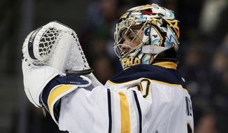 Buffalo Sabres goalie Ryan Miller checks his glove after giving up goal to the Colorado Avalanche in the second period of an NHL hockey game in Denver, Saturday, Feb. 1, 2014. (AP Photo/David Zalubowski)