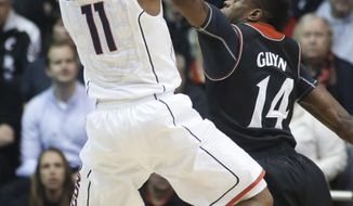 Connecticut guard Ryan Boatright (11) shoots against Cincinnati guard Ge'Lawn Guyn (14) during the first half of an NCAA college basketball game, Thursday, Feb. 6, 2014, in Cincinnati. (AP Photo/Al Behrman)