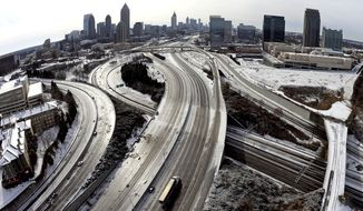 """FILE -In this Wednesday, Jan. 29, 2014 file photo, In this aerial photo taken with a fisheye lens looking south toward downtown Atlanta, the ice-covered interstate system shows the remnants of a winter snow storm, in Atlanta. Less than nine days after a storm trapped commuters in cars and children on school buses in metro Atlanta, state officials say they """"overreacted"""" to information from federal forecasters and posted incorrect information on giant message boards over freeways. (AP Photo/David Tulis, File)"""