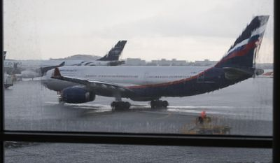 ** FILE ** In this Monday, July 8, 2013, file photo, an airplane of Aeroflot flight rolls out in preparation for a takeoff seen through a window of Sheremetyevo airport outside Moscow, Russia. (AP Photo/Alexander Zemlianichenko, file)