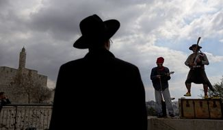 An ultra-Orthodox Jewish man looks at street performers as the play music near the Tower of David in Jerusalem's old city, Thursday, Feb. 6, 2014. (AP Photo/Sebastian Scheiner)