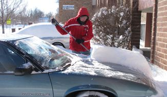 Pat Firebaugh, an investigator for the Kansas attorney general's office, cleans snow off his car outside his apartment, Wednesday, Feb. 5, 2014, in Topeka, Kan. State government offices closed because of a winter storm that dumped more than a foot of snow in the area. (AP Photo/John Hanna)