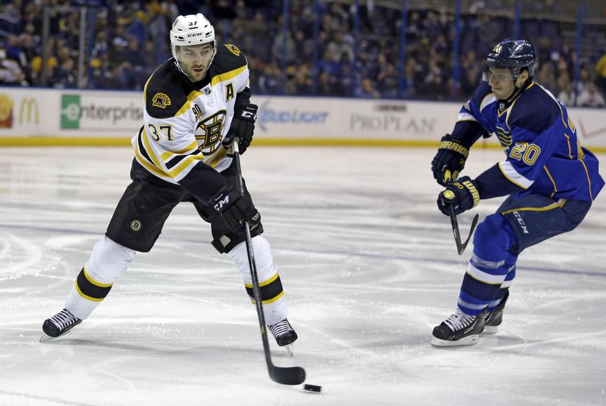 Boston Bruins' Patrice Bergeron, left, handles the puck as St. Louis Blues' Alexander Steen watches during the first period of an NHL hockey game Thursday, Feb. 6, 2014, in St. Louis. (AP Photo/Jeff Roberson)