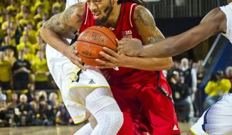 Michigan guard Nik Stauskas, top, steps into a block of Nebraska forward Terran Petteway in the first half of an NCAA college basketball game in Ann Arbor, Mich., Wednesday, Feb. 5, 2014. (AP Photo/Tony Ding)