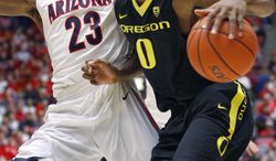 Oregon's Mike Moser (0) maneuvers with the ball against Arizona's Rondae Hollis-Jeffson (23) in the first half of an NCAA college basketball game Thursday, Feb. 6, 2014, in Tucson, Ariz. (AP Photo/John MIller)