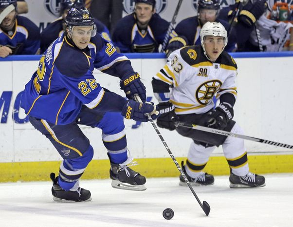 St. Louis Blues' Kevin Shattenkirk, left, and Boston Bruins' Brad Marchand chase after a loose puck during the second period of an NHL hockey game Thursday, Feb. 6, 2014, in St. Louis. (AP Photo/Jeff Roberson)