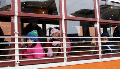 Fairview Elementary School first graders peer through the windows of the Fort Smith Trolly as an unusual snow began to blanket the area during a class field trip to the Fort Smith Museum of History, Thursday, Feb. 6, 2014.  (AP Photo/The Southwest Times Record, Rachel Rodemann)