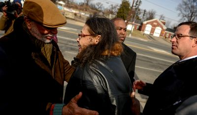 Neighbor Frank Wilds, left, gives his condolences to Sandra Mills, center, the widow of the late Medric Cecil Mills, Jr., 77, following a press conference at the site where Mills died of a heart attack along Rhode Island Avenue in Northwest after firefighters refused to help him even though he was across the street from the Engine 26 Fire Station, Washington, D.C., Thursday, February 6, 2014. (Andrew Harnik/The Washington Times)