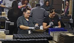FILE - In this Feb. 28, 2013 file photo, workers assemble 30-round capacity ammunition magazines for high-velocity rifles, inside the Magpul Industries plant in Erie, Colo. Magpul, one of the country's largest producers of ammunition magazines for guns, is leaving Colorado and moving operations to Wyoming because of Colorado laws that include restrictions on how many cartridges a magazine can hold. The Wyoming State Loan and Investment Board is considering a $13 million incentive package to help Magpul make the move. (AP Photo/Brennan Linsley, File)