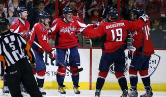 Washington Capitals right wing Alex Ovechkin, center, celebrates his goal with defenseman Karl Alzner, left; left wing Martin Erat (10), from the Czech Republic; center Nicklas Backstrom (19), from Sweden; and defenseman John Carlson (74) during the third period of an NHL hockey game, Thursday, Feb. 6, 2014, in Washington. It was Ovechkin's 40th goal of the season. The Capitals won 4-2. (AP Photo/Alex Brandon)