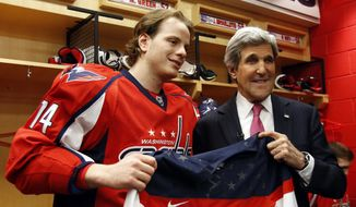Secretary of State John Kerry, right, poses for a photograph holding the team USA hockey jersey with Washington Capitals defenseman John Carlson, in the locker room before their game with the Winnipeg Jets, Thursday, Feb. 7, 2014, in Washington. Kerry was greeting players that have been selected for their country's Olympic hockey team. (AP Photo/Alex Brandon, Pool)